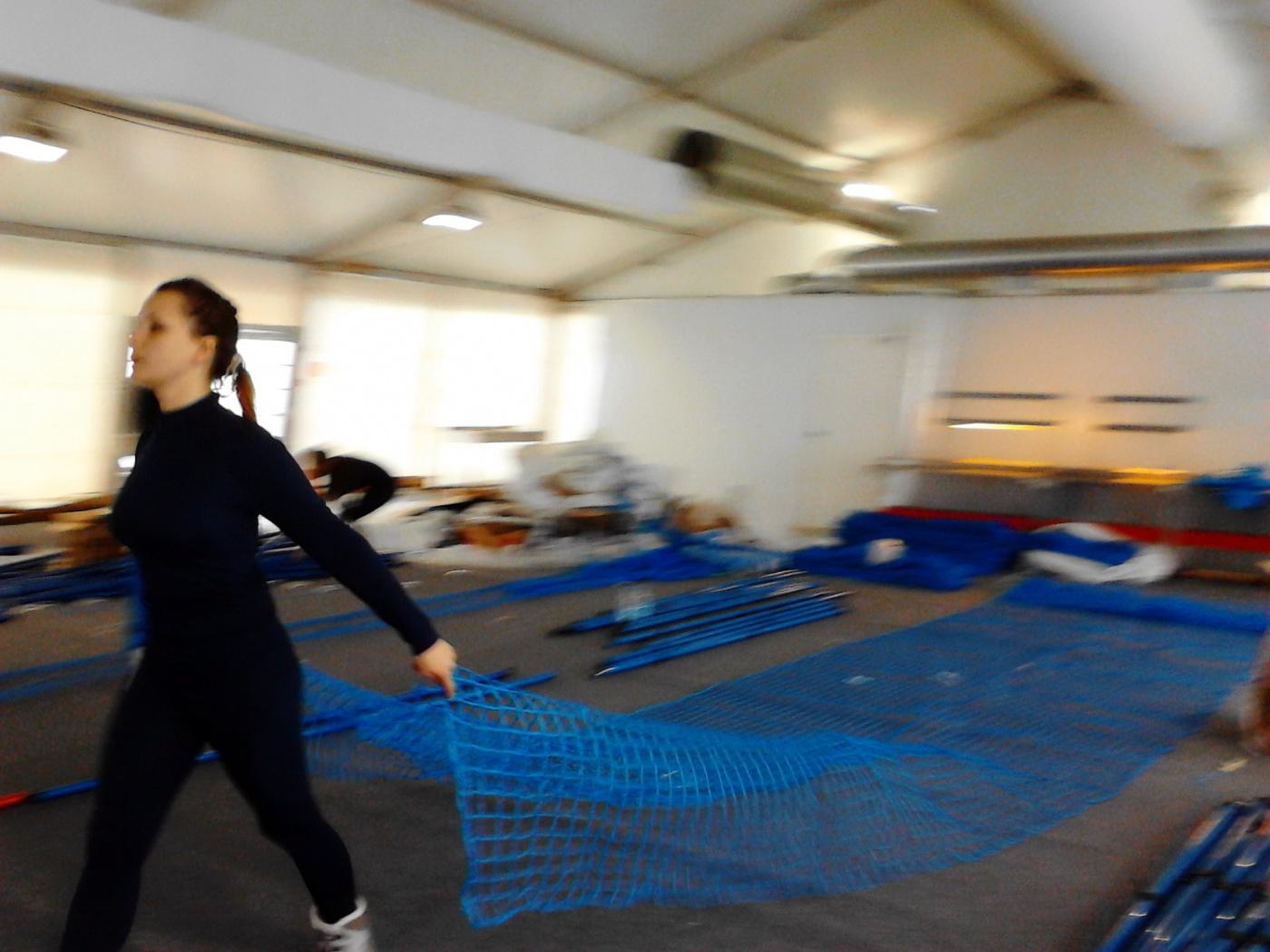 Маша растягивает на полу заготовку сетки, чтобы прикрепить к ней палки с крючками